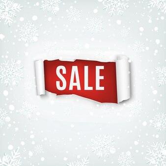 Verkauf. zerrissenes papperbanner auf winterhintergrund mit schnee und schneeflocken.