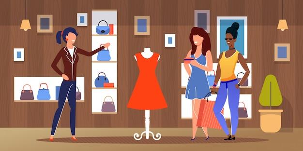 Verschiedene freundinnen, die am bekleidungsgeschäft kaufen