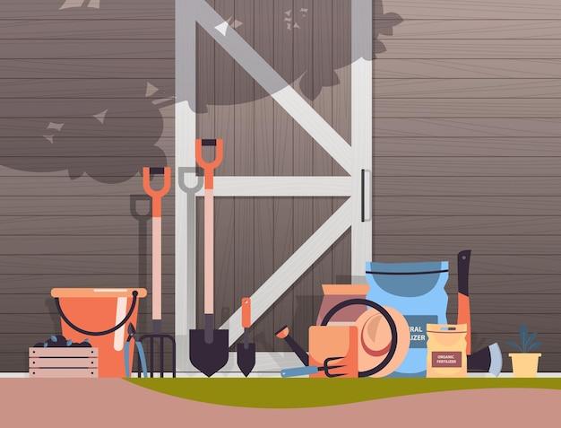 Verschiedene garten- und landwirtschaftliche werkzeuge gartengeräte in der nähe von holzscheunentüren öko-landwirtschaft landwirtschaftskonzept illustration