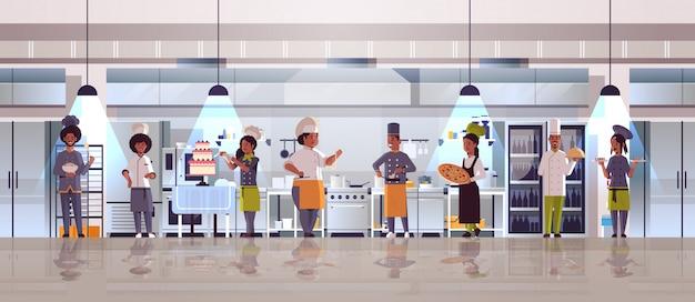 Verschiedene köche, die zusammen afroamerikanische männerfrauen r im einheitlichen kochenden nahrungsmittelkonzept des modernen restaurantkücheninnenraums stehen