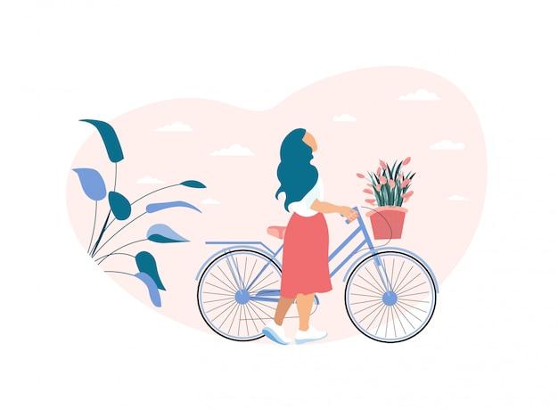 Verträumte frau rollt fahrrad mit blumenkorb