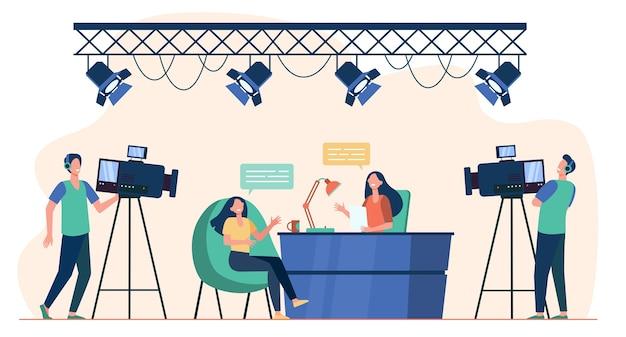 Videografen drehen interview im fernsehstudio. nachrichtenmoderator im gespräch mit dem gast der tv-show. flache vektorillustration für kamerateam, rundfunk, fernsehkonzept