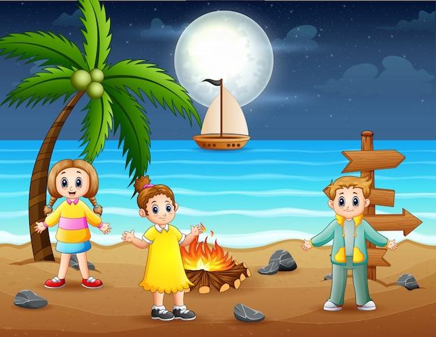 Viele kinder mit lagerfeuer am strand