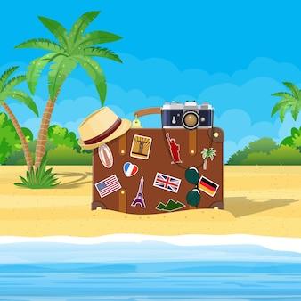 Vintage alter reisekoffer am strand. retro-tasche aus leder mit aufklebern. hut, fotokamera, brille, inselpalmenkokosnuss. sandstrand, meer, wolke. urlaubsreisen. eben