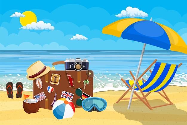 Vintage alter reisekoffer am strand. retro-tasche aus leder mit aufklebern. hut, fotokamera, brille, kokos