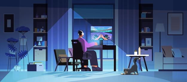Virtueller spieler, der online-videospiel auf computermann in kopfhörern spielt, die vor der horizontalen vektorillustration des monitor-nachtwohnzimmers in voller länge sitzen
