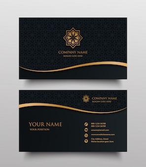 Visitenkarte mit goldblumen-zierlogo und platz für text auf dunklem hintergrund