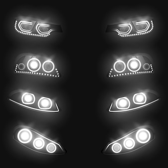 Vordere und hintere scheinwerfer des autos, die im realistischen satz der dunkelheit lokalisiert auf schwarzem hintergrund weiß glühen.