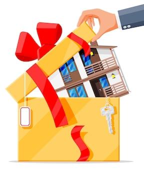 Vorstadtfamilienhaus in geschenkbox mit schlüssel, band und bogen. landschaft holzhaus gebäude vorhanden symbol. immobilien und miete. cartoon-vektor-illustration im flachen stil