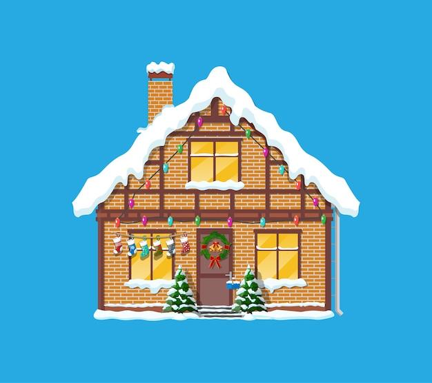 Vorstadthaus bedeckt schnee. gebäude in feiertagsverzierung. weihnachtsbaumfichte, kranz. frohes neues jahr dekoration. frohe weihnachten. neujahrs- und weihnachtsfeier.