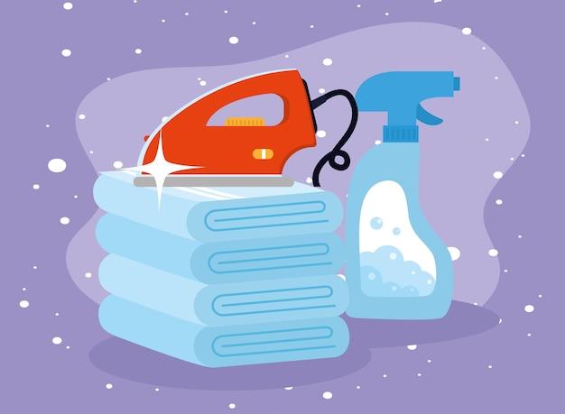 Wäschebügeleisen auf handtüchern und waschmittelspray auf violettem hintergrund