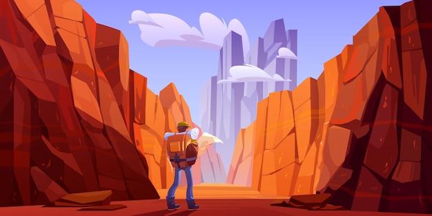 Wanderer mann mit karte auf wüstenstraße in der schlucht