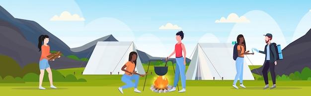 Wanderergruppe, die spaß beim zubereiten von essen im kochenden topf des bowlers am lagerfeuer-wanderkonzeptmix-rennreisenden auf wanderzeltcampingplatz-landschaftshintergrund flach horizontal hat