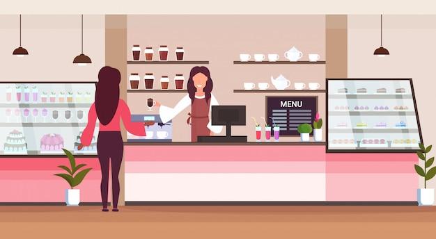 Weibliche barista-coffeeshop-arbeiterin, die kundin dient, die glas der kellnerin des heißen getränks gibt, das an der modernen horizontalen cafeteria-innenwohnung des cafés steht