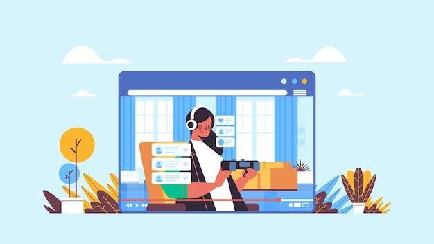 Weibliche blogger aufzeichnung spielprozess online-blog live-streaming blogging-konzept mädchen im webbrowser-fenster spielen videospiele wohnzimmer innen horizontales porträt