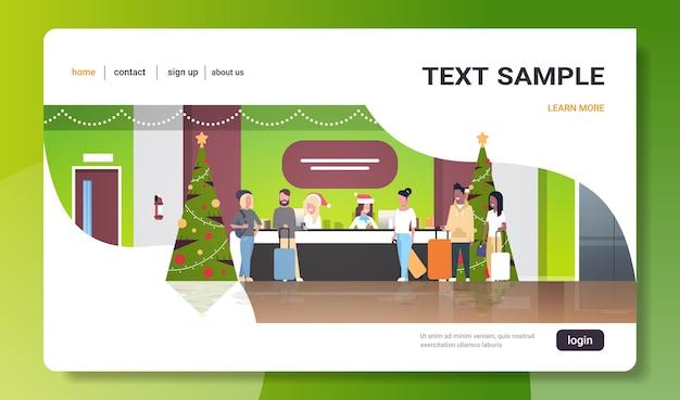 Weibliche empfangsmitarbeiter in weihnachtsmützen treffen touristen mit gepäck an der empfangsschalterregistrierung weihnachtsferienkonzept moderne hotellobby-landingpage