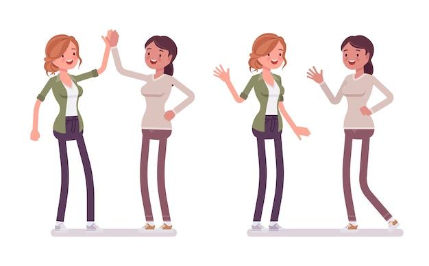 Weibliche glückliche enge freunde geben high five und winken
