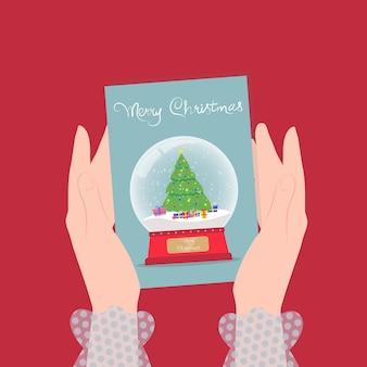 Weibliche hände der weihnachtsillustration halten eine grußkarte mit einer schneebedeckten glaskugel
