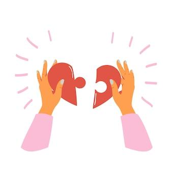 Weibliche hände hält und faltet stücke des herzens puzzlespiel