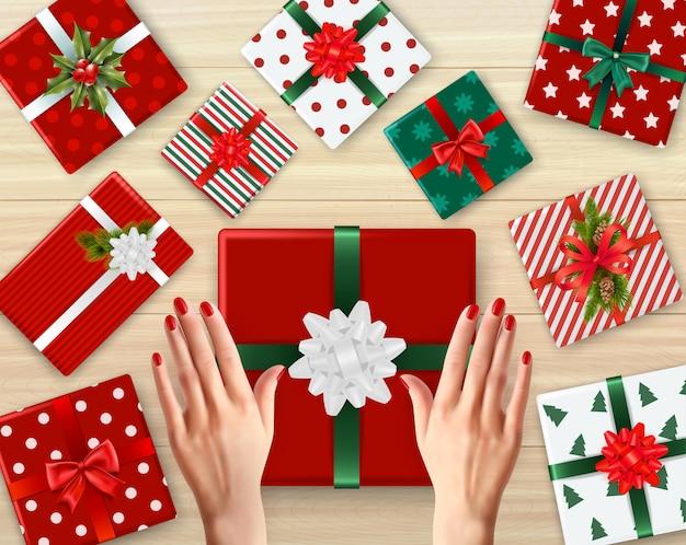 Weibliche hände und verzierte geschenkboxen aus pappe mit realistischem hintergrund unterschiedlicher farbe