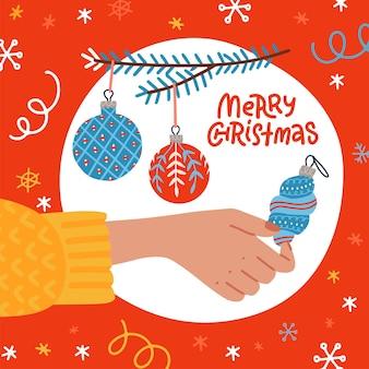 Weibliche hand, die einen blauen dekorativen weihnachtsflitter hält. quadratische grußkarte mit kugeln auf tannenzweig und beschriftungstext - frohe weihnachten. flache gezeichnete illustration des vektors hand.