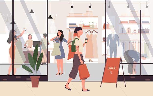 Weibliche modeverkäufe an der jungen frau des einkaufszentrums, die neben ladengeschäft oder boutique geht