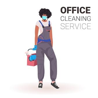 Weibliche professionelle büroreinigerin hausmeisterin in medizinischer maske mit reinigungsausrüstung kopienraum