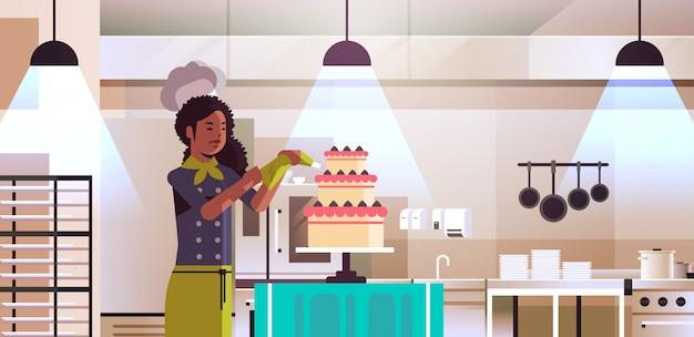 Weibliche professionelle kochgebäck koch dekorieren leckere hochzeitscremetorte afroamerikanerin in einheitlichen kochnahrungskonzept modernes restaurant küche innenporträt