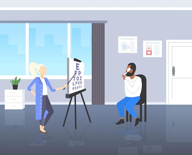 Weiblicher augenarzt, der das sehvermögen des afroamerikanischen mannes des patienten-sehvermögensarztes in einheitlichen hinweisbuchstaben am diagrammklinik-gesundheitskonzept des modernen klinikrauminnenraums in voller länge überprüft