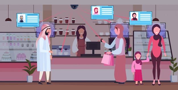Weiblicher barista-coffeeshop-arbeiter, der arabischen kundenklienten dient gesichtserkennung konzept überwachungskameraüberwachung cctv-system moderne cafeteria innenraum in voller länge horizontal