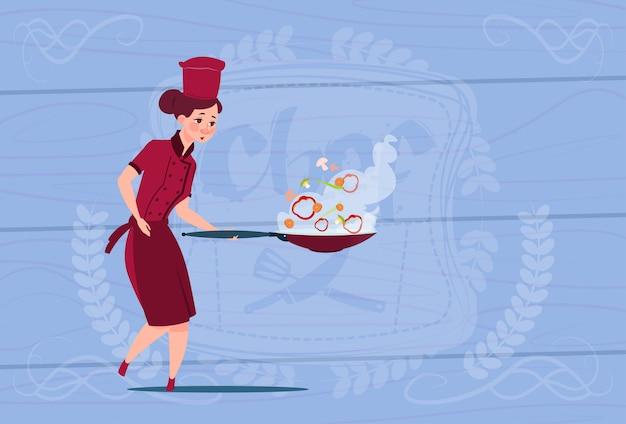 Weiblicher chef cook holding brying pan-karikatur in der restaurant-uniform über hölzernem strukturiertem hintergrund