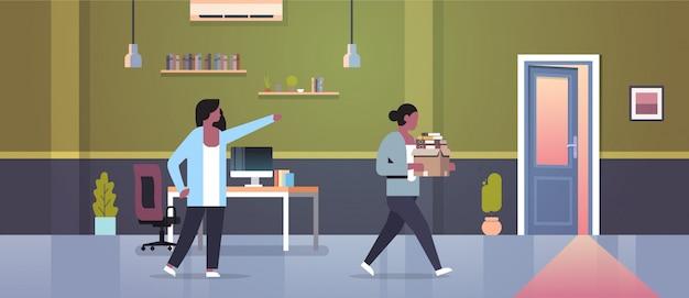 Weiblicher chef entlässt das zeigen des fingers auf tür abgefeuerten frauenangestellten mit flachem modernem büroinnenraum des papierdokumentenkastenentlassungsarbeitslosen-konzeptes