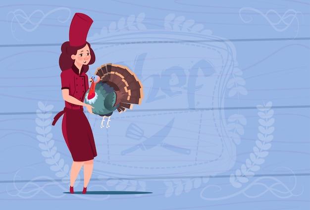 Weiblicher chef-koch holding turkey cartoon-chef in der restaurant-uniform über hölzernem strukturiertem hintergrund