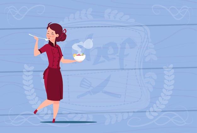 Weiblicher chef-koch tasting soup cartoon-chef in restaurant uniform über hölzernem strukturiertem hintergrund
