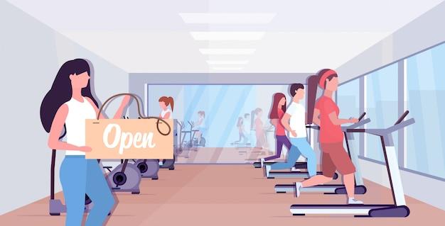 Weiblicher fitnesstrainer, der offenes schild hält