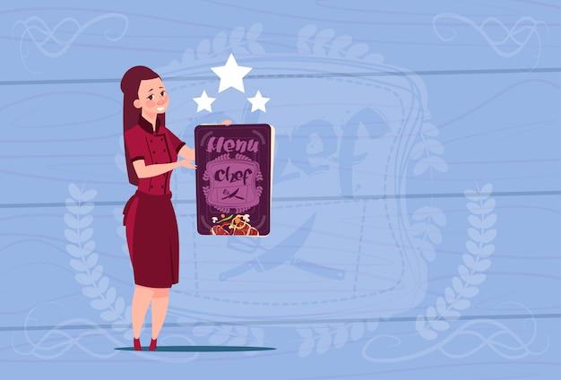 Weiblicher koch holding best chef award glücklicher karikatur-chef in der restaurant-uniform über hölzernem strukturiertem hintergrund