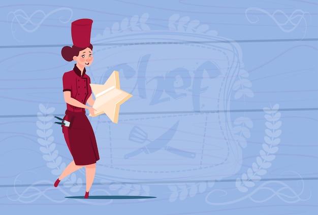 Weiblicher koch holding star best chef award-glücklicher karikatur-chef in der restaurant-uniform über hölzernem strukturiertem hintergrund