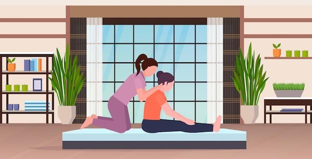 Weiblicher persönlicher trainer, der dehnungsübungen mit dem fitnesslehrer des mädchens macht, der frau hilft, muskeln zu trainieren trainingskonzept modernes yoga studio gym innenraum flach in voller länge horizontal