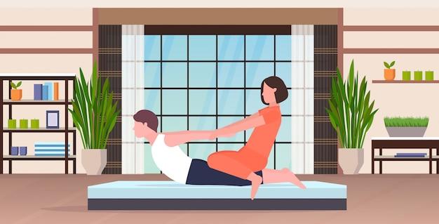 Weiblicher persönlicher trainer, der dehnungsübungen mit kerl fitnesslehrer macht, der mann hilft, muskeln zu trainieren trainingskonzept modernes yoga studio gym innenraum flach in voller länge horizontal