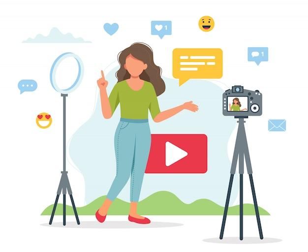 Weiblicher video-blogger, der video mit kamera und licht aufzeichnet.