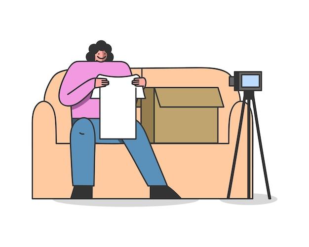 Weiblicher video-blogger-influencer, der kaufkleidung auspackt und überprüft