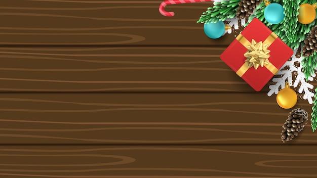 Weihnachten 3d hintergrund mit geschenkbox, kiefer, ball, süßigkeiten und schneeflocke auf holz