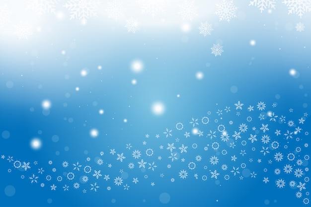 Weihnachts- und des neuen jahreshintergrund mit schneeflocken und lichteffekten auf einen blauen hintergrund.