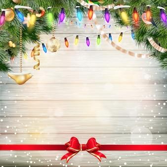Weihnachtsdekoration mit tannenzweigen auf weißem holzbrett.