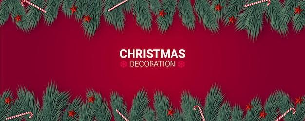 Weihnachtsdekorationszusammensetzung auf rotem hintergrund mit tannenzweigen