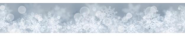 Weihnachtsfahne von verschwommenen schneeflocken auf grauem hintergrund