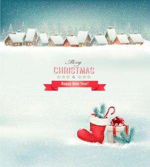 Weihnachtsfeiertagshintergrund mit einem dorf, einem stiefel und einer geschenkbox.
