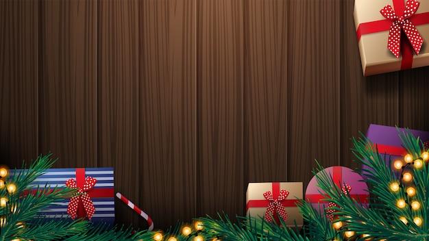 Weihnachtsgeschenke, weihnachtsbaumast und gelbe girlande auf holztisch, draufsicht. hölzerner weihnachtshintergrund