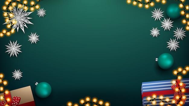 Weihnachtsgrüner hintergrund für ihre künste mit girlande, grünen bällen, geschenken und papierschneeflocken, draufsicht