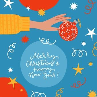 Weihnachtsgrußkarte verziert mit konfettikugel serpentin und sternen weibliche hand hält weihnachten...